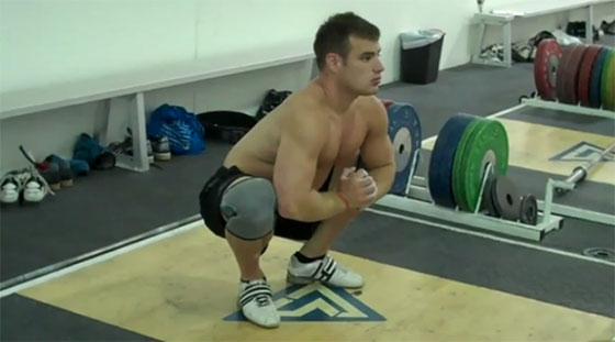 Man squatting down without weights