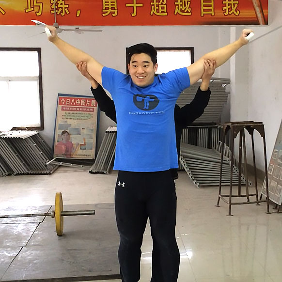 Coach Fang internally rotating my shoulders into the proper overhead position