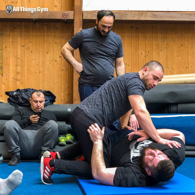 Lasha being forcibly restrained after breaking down while trying to make sense of the poorly-worded IWF qualification document.